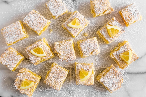 These sweet homemade lemon bars are perfect for spring. Full of tart lemon flavor and made with a sweet shortbread crust. Always a crowd pleaser and delicious for snacking.