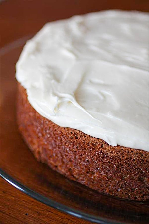 carrot cake with creamy cream cheese frosting on a glass plate