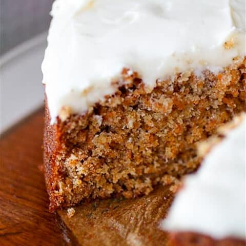 carrot cake with creamy cream cheese frosting cut with one slice missing