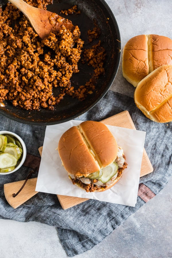 These sloppy Cubanos are the perfect spin to the traditional Sloppy Joe. A delicious mixture of ground pork, chorizo, spices, lime, and tomato piled high on a bun and topped with Swiss cheese and pickles. It's the perfect mashup of a Cuban sandwich and Sloppy Joe.