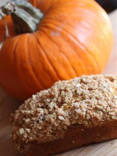 crumble topped pumpkin bread with a pumpkin in the background