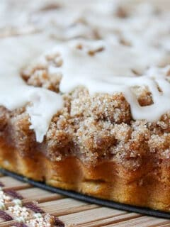 pumpkin coffee cake with brown butter glaze sitting on a pie plate