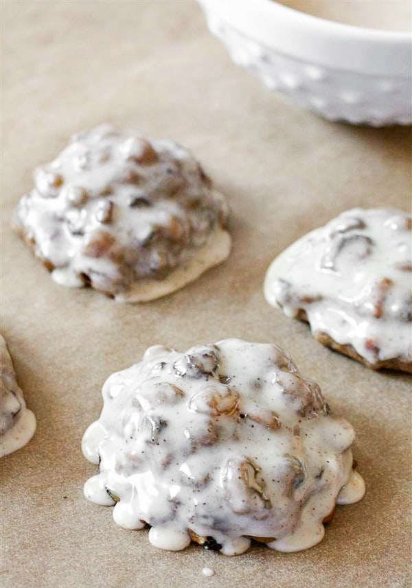 fruit cake cookies with icing sitting on parchment paper