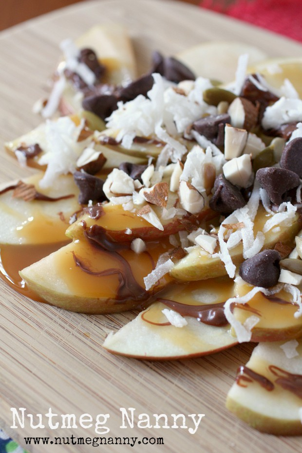 apple nachos on a wooden plate topped with nuts, coconut and chocolate.