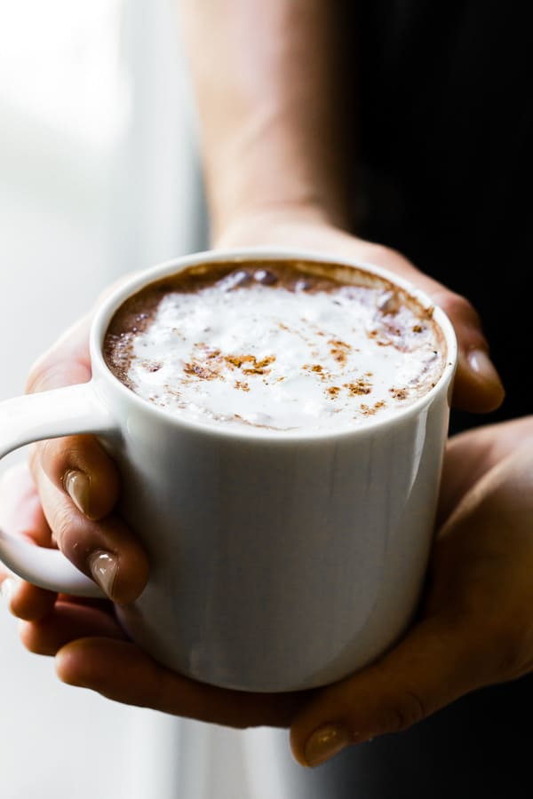 Holding a mug of Vitamix hot chocolate
