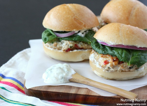 These Greek chicken burgers are slathered with Greek yogurt sauce and and homemade quick pickled red onions. This sandwich is packed full of flavor!
