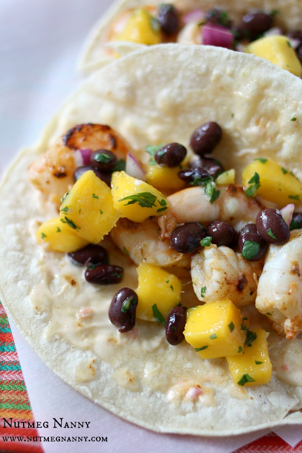 These marinated shrimp tacos with chili mustard aioli are the perfect summertime taco. Packed full of flavor and covered with a sweet mango black bean salsa.
