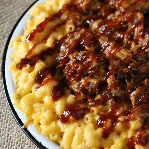 pulled pork mac and cheese in a white dish drizzled with bbq sauce