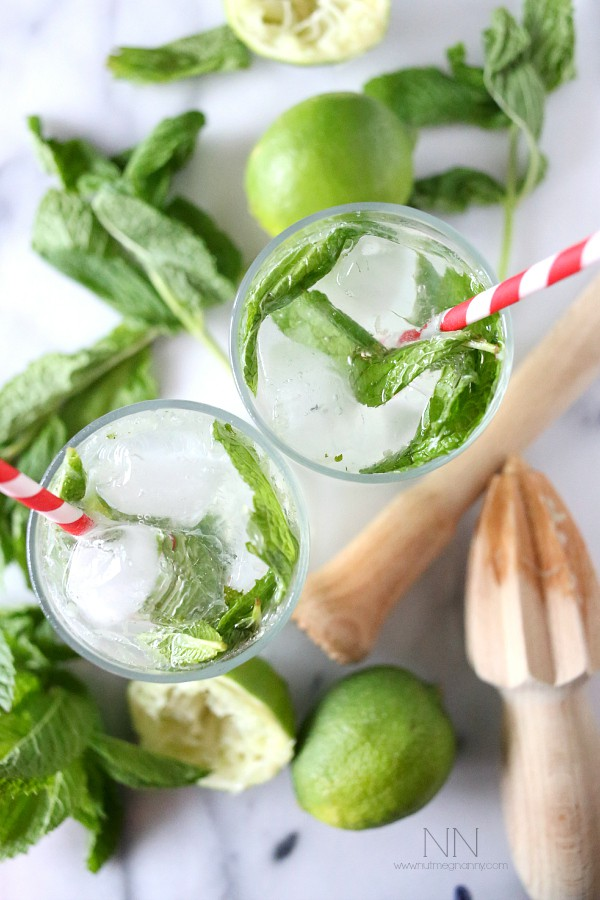coconut mojitos in a tall cocktail glass surrounded by fresh mint and limes