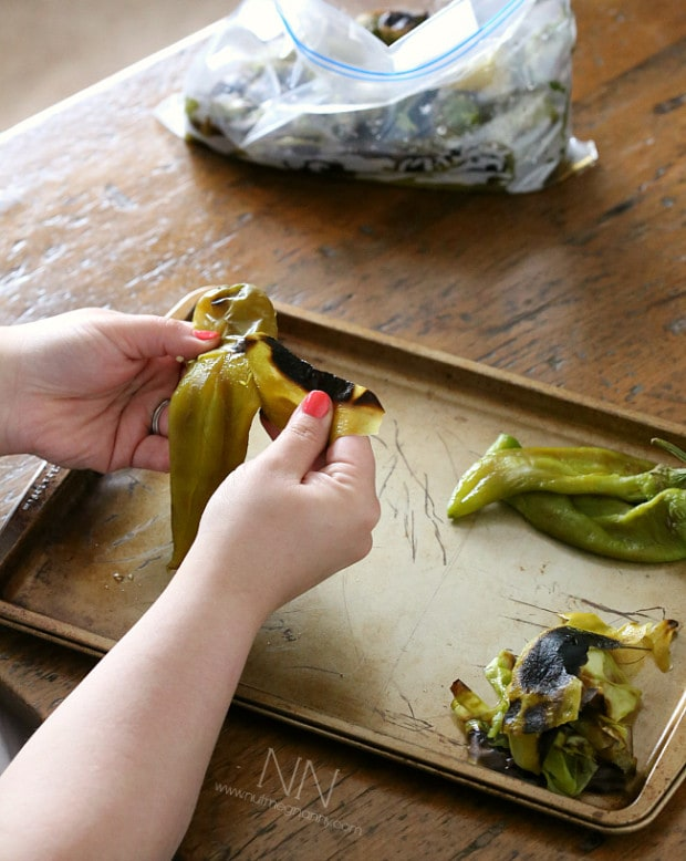 peeling off the charred skin on a roasted hatch green chiles