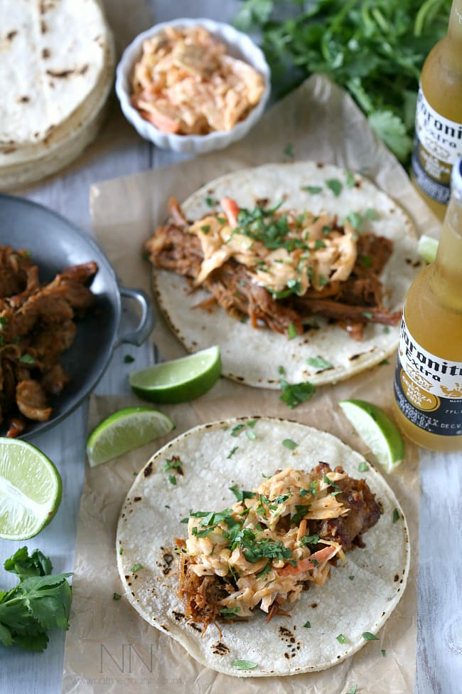 These slow cooker ginger beer pulled pork tacos are topped with a spicy chipotle cole slaw and served on toasted corn tortillas.