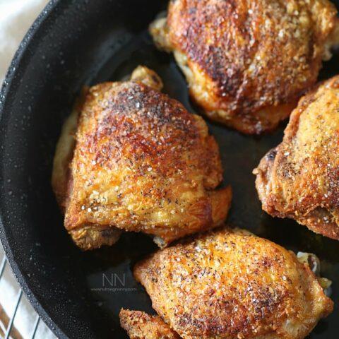 crispy pan roasted chicken thighs in a skillet sprinkled with kosher salt