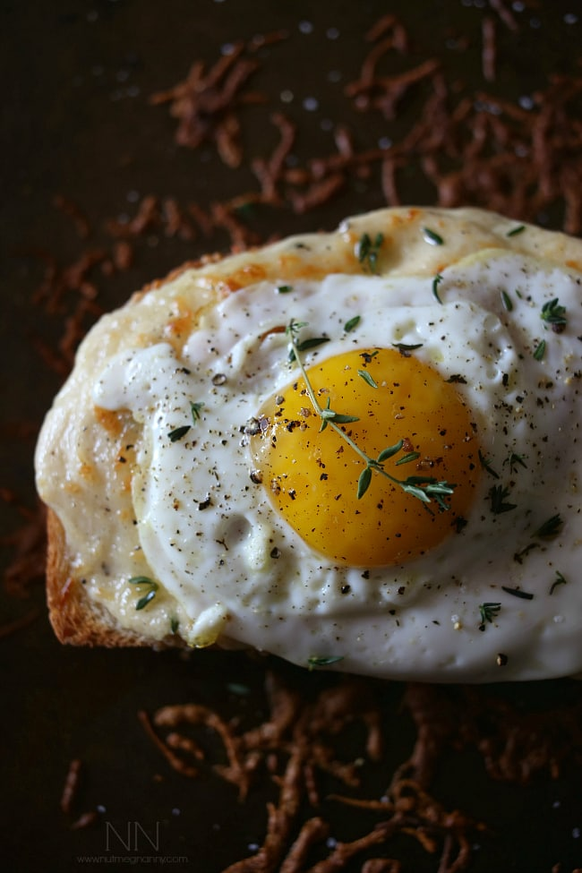 This croque madame is the perfect combination of bechamel cheese sauce, Canadian bacon and Swiss cheese stuffed between two slices of crusty bread and topped with a fried egg. Perfect for breakfast or dinner.