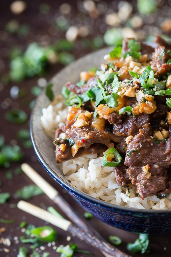 Say hello to your new favorite 25 minute meal. This spicy beef with peanuts is super easy and combines quick marinaded beef, peanuts and cilantro over top light brown basmati rice.