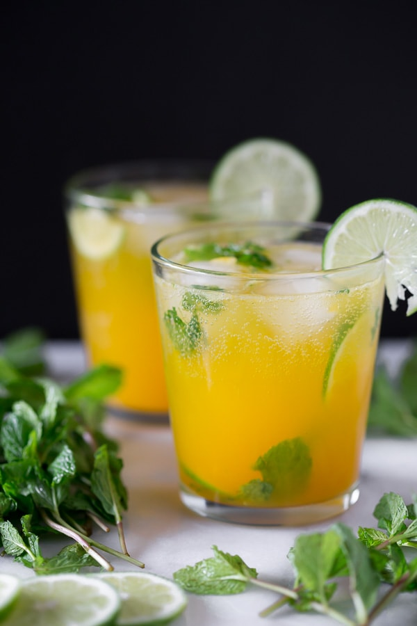 mango mojito in a short cocktail glass garnished with fresh lime and mint