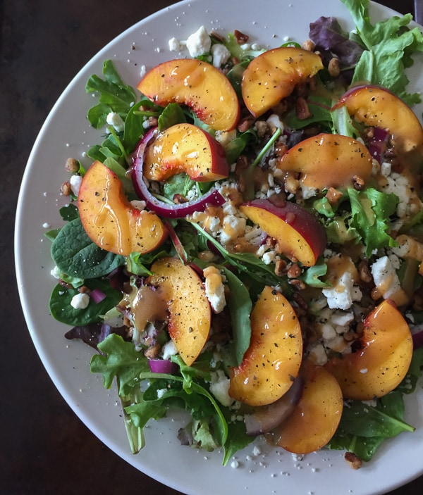 This peach feta salad with peach vinaigrette is the perfect way to celebrate summer. Baby greens, fresh peaches, feta, red onion, praline pecans and perfectly sweet peach puree vinaigrette.