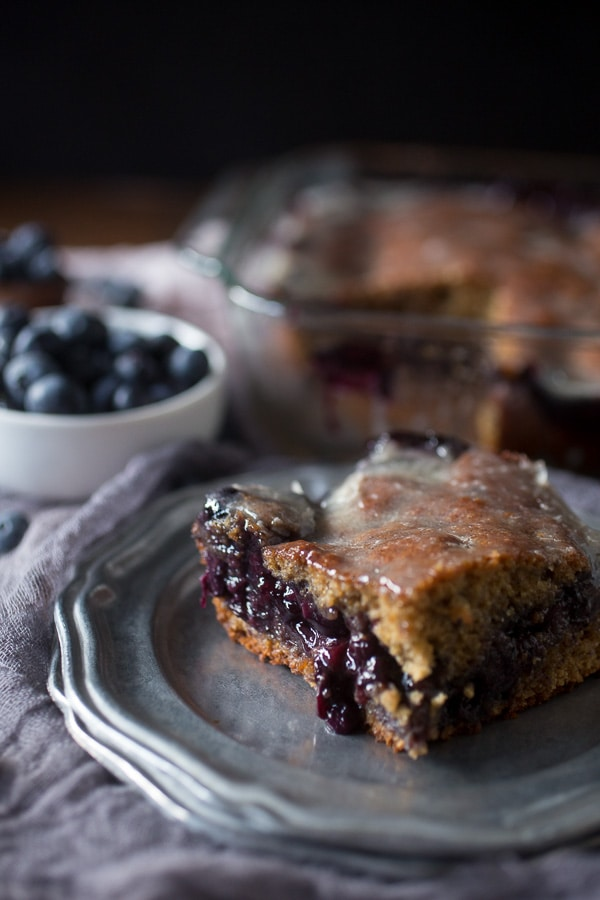 This blueberry fritter cake is the perfect way to celebrate the bounty of summer - sweet cinnamon scented cake with a warm blueberry center topped with vanilla bean glaze. It's like you favorite bakery fritter but in easy to make cake form. Trust me, you'll love the taste of the cake and it's perfect for breakfast or dessert.