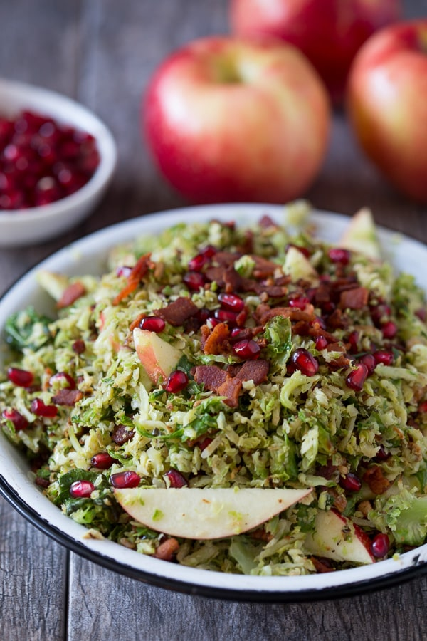 This shaved Brussels sprout apple bacon salad is the perfect combo of sweet, salty and savory. Roasted and shaved Brussels sprouts combined with bacon, candied pecans, sliced apples and pomegranates seeds all drizzled with a simple maple vinaigrette.