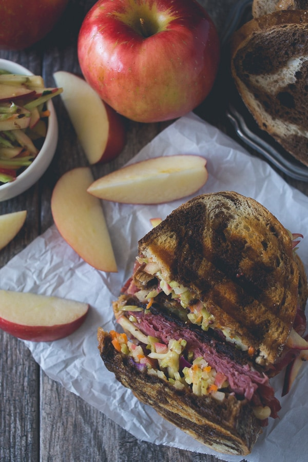 This tangy apple slaw corned beef reuben is the perfect fall sandwich. Perfectly toasted marble rye topped with an apple cabbage slaw, corned beef, melted swiss cheese and lots of homemade Russian dressing.