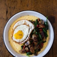 This cheesy polenta sausage breakfast bowl is packed with flavor. It starts with cheesy polenta topped with spinach, sun dried tomatoes, chicken sausage and topped with a crispy fried egg. Never skip breakfast again!