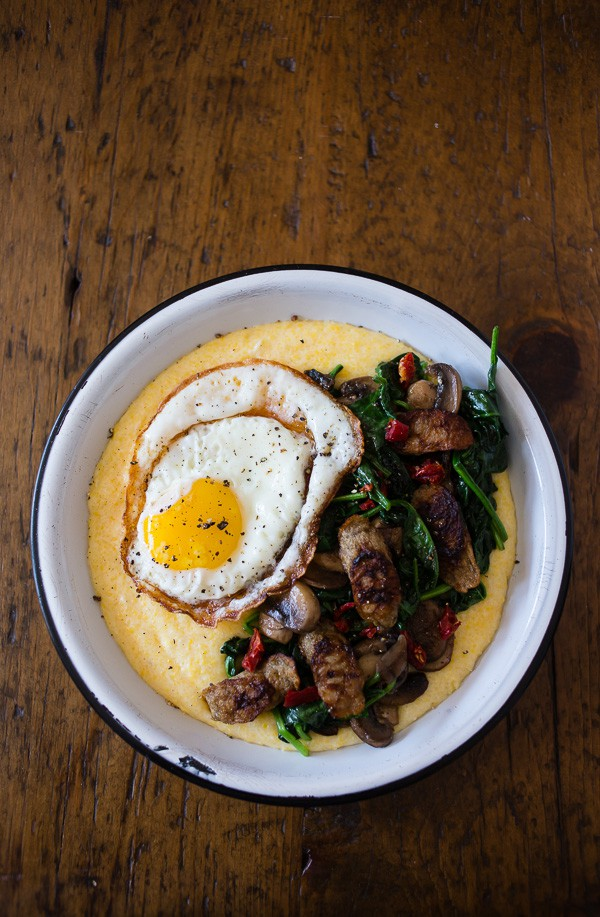 This cheesy polenta sausage breakfast bowl is packed with flavor. It starts with cheesy polenta topped with spinach, mushrooms, sun dried tomatoes, chicken sausage and topped with a crispy fried egg. Never skip breakfast again!