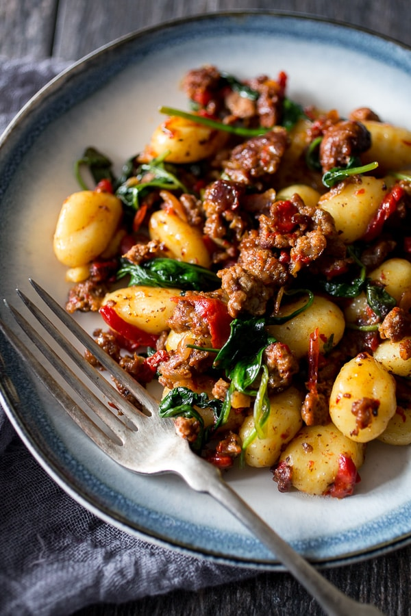 chorizo roasted red pepper spinach gnocchi on a plate with a fork