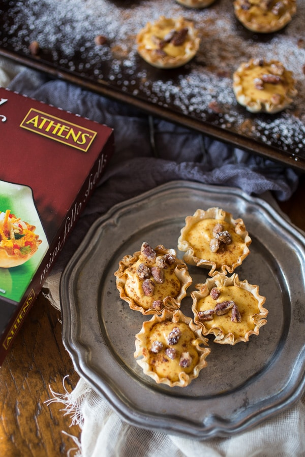 These no bake pumpkin cheesecake phyllo bites are the easiest Thanksgiving dessert ever. Fluffy spiced pumpkin cheesecake filled into crunchy phyllo shells and topped with spiced nuts. You'll love these sweet little bites!