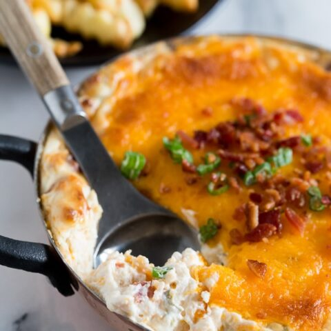 This warm loaded baked potato dip is served warm and full of delicious flavor. Packed full of cream cheese, sour cream, green onions, bacon and of course CHEESE! Perfect when served with french fries or potato chips!