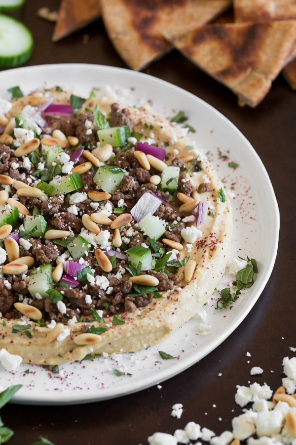 This Greek topped hummus is packed full of flavor. Topped with spiced lamb, cucumber, red onion, pine nuts, feta cheese, mint and a sprinkling of sumac. Serve with pita chips and DIG IN!