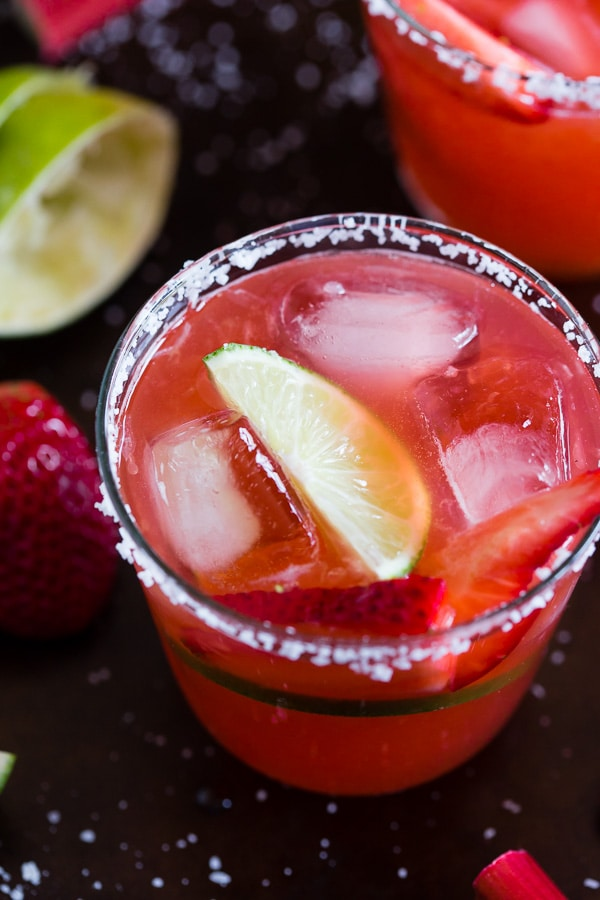 This strawberry rhubarb margarita is the perfect way to celebrate spring and Cinco de Mayo. The perfect balance of sweet, tart and tequila! Made with a homemade strawberry rhubarb syrup and served perfectly chilled on the rocks with a salted rim. Cheers to your new summer drink!
