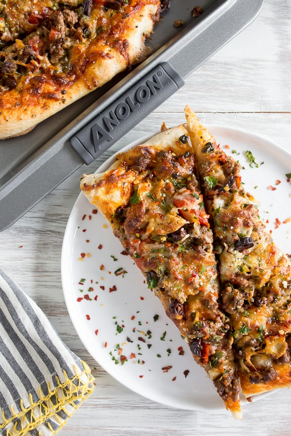 This beef puttanesca pizza is the perfect gourmet pizza night option. Fully loaded with tons of flavor and ready in just 30 minutes. You'll love this delicious pasta sauce pizza twist.