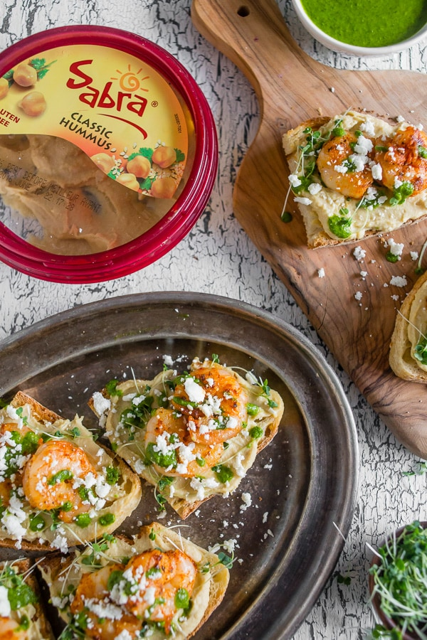 This cajun shrimp hummus crostini is the perfect summer appetizer. Toasted bread topped with hummus, micro greens, spicy cajun shrimp, cilantro pesto and a sprinkling of feta cheese. Hello, summer!