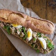 This pesto tuna baguette sandwich is the perfect summer sandwich. Fresh basil pesto mixed with olive oil canned yellowfin tuna and piled high on a baguette with arugula and hard boiled eggs. You'll love this sandwich!