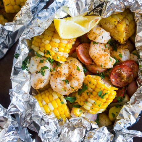low country boil foil packets on a sheet pan wrapped in foil