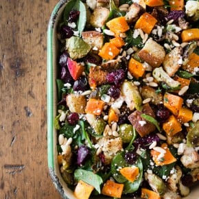 This fall panzanella salad is packed full of fresh roasted vegetables, dried cranberries, pine nuts, feta cheese, buttery toasted gluten free bread and drizzled with a maple syrup herb vinaigrette. This salad is 100% fall and perfect for the holidays!