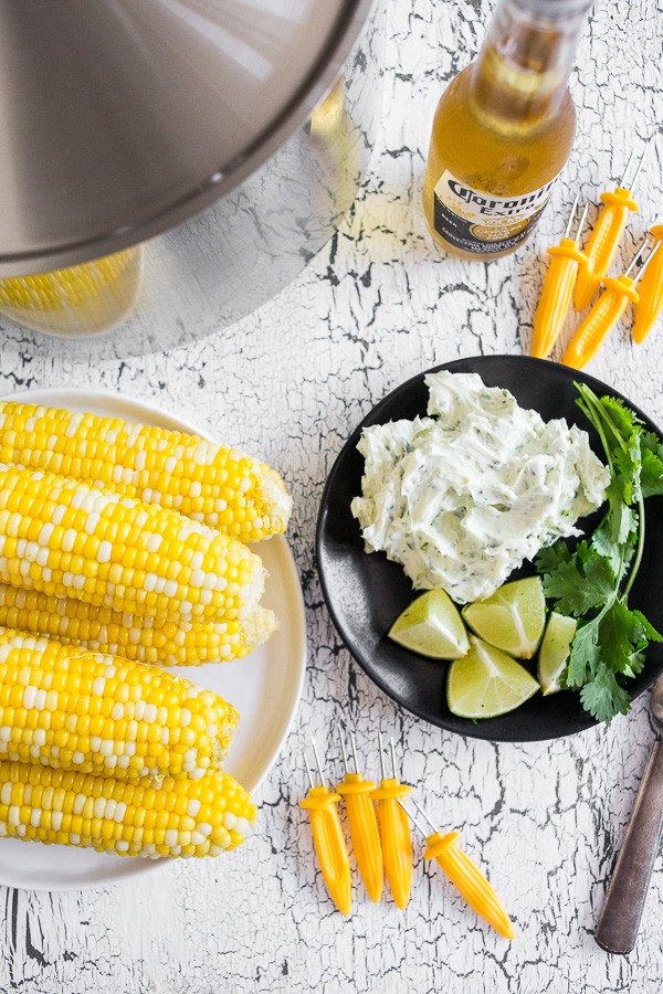 This beer steamed corn on the cob is slathered with homemade honey cilantro citrus butter. This side dish is crazy delicious and a perfect use for fresh from the farm corn or any fresh corn you hoarded during the summer and froze.
