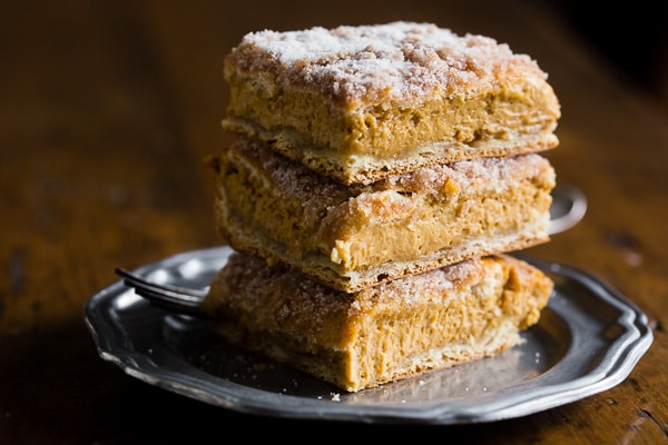 These pumpkin churro cheesecake bars are going to be your new favorite fall treat! A fun twist to pumpkin cheesecake with a crispy pumpkin spice sugar crescent roll topping. Super easy to make and perfect for all your holiday dessert tables!