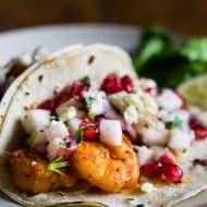 These shrimp tacos with apple pomegranate salsa are the perfect balance of sweet and heat. The shrimp are sauteed in cajun seasoning and topped with a delicious salsa made from apples, pomegranates, red onion, cilantro and lime. You'll love these super easy and crazy delicious tacos.