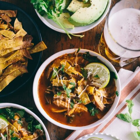 chicken and chard tortilla soup in a bowl surrounded by toppings and a beer