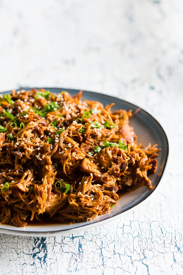 This slow cooker honey soy sriracha pulled chicken is packed full of flavor and made all in the slow cooker. All you need are a few easy ingredients, a slow cooker and 4-6 hours. Serve it over rice, on a bun or straight from the slow cooker!