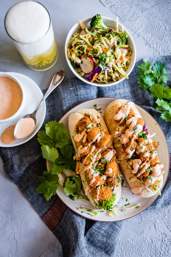 This Asian shrimp po boy sandwich is packed full of flavor and perfect for the busy weeknight meal planning. First, you take a crusty roll and pack it full of a crunchy Asian flavored broccoli slaw, top with crispy baked shrimp and drizzle with spicy Sriracha mayo. You'll love this sandwich!