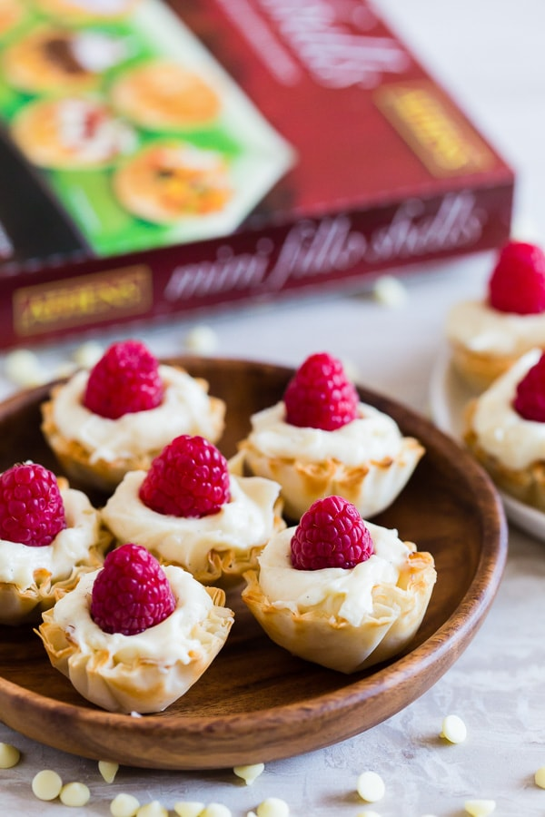 These no bake white chocolate cheesecake phyllo bites are perfectly adorable and topped with fresh raspberries. They are super simple to make and would look perfect on your holiday dessert table.