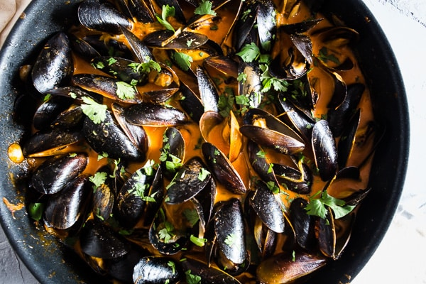 These red curry coconut milk mussels are ready in just 35 minutes and are packed full of ginger, garlic, and lemongrass flavors. You'll be blown away by how easy they are to make and want to sop up every last drop of the red curry coconut milk sauce!