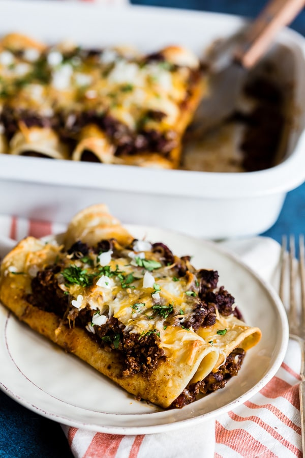 These chipotle ground beef enchiladas are made with homemade chipotle beef chili and rolled up in corn tortillas and covered with cheddar cheese. The best part is you can make the chili days before making to help cut down on prep time. If you have never made enchiladas before now is the time!
