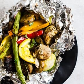 This chicken sausage and vegetable foil packet dinner is super simple to make and perfect for summer. Packed full of chicken sausage, sweet peppers, zucchini, yellow squash, red onion, green beans and drizzled with a herbed olive oil. You'll love this simple dinnertime recipe!