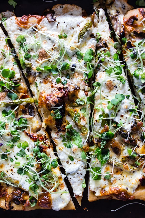 This asparagus mushroom burrata pizza cooks up in less than 20 minutes and is the perfect spring pizza. Topped with lots of sauteed mushrooms, asparagus, sun-dried tomatoes, mozzarella cheese, burrata cheese and sprinkled with red pepper flakes and micro greens. You'll LOVE this pie!
