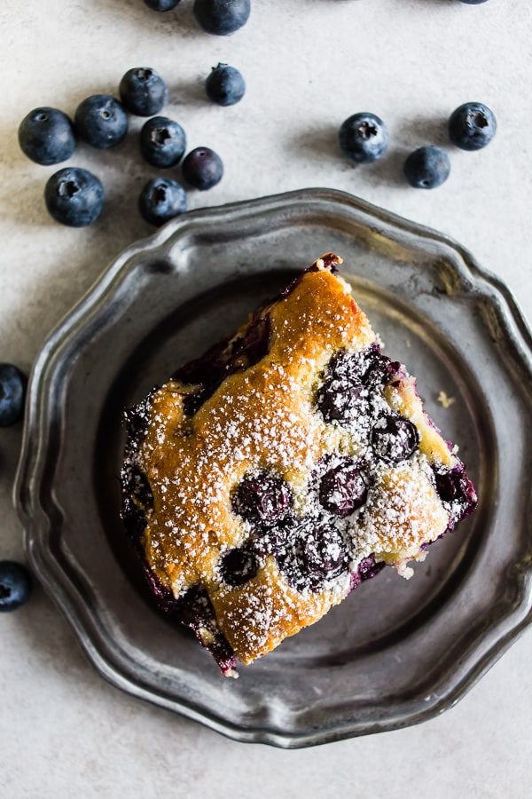 This blueberry lemon ricotta olive oil cake is the perfect snacking cake. Sprinkled with a little powdered sugar and great for breakfast or dessert! Plus the cake is super moist and crazy easy to make! You'll want to get into the kitchen and make this cake asap!