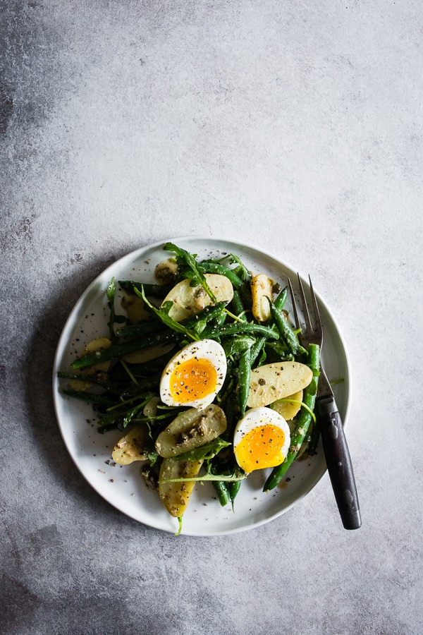 This tangy green bean potato salad is the perfect combination of buttery fingerling potatoes, crunchy blanched green beans, peppery arugula and soft boiled eggs all tossed in a creamy Dijon and caper vinaigrette. It's tangy, perfect for hot summer nights and makes an amazingly fast and easy meatless dinner!