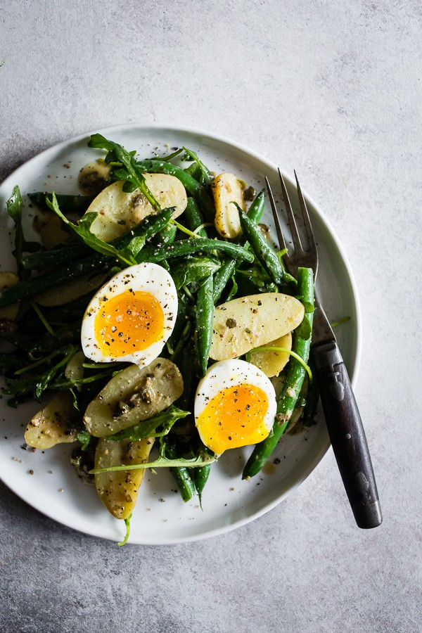 This tangy green bean and potato salad is the perfect combination of buttery fingerling potatoes, crunchy blanched green beans, peppery arugula and soft boiled eggs all tossed in a creamy Dijon and caper vinaigrette. It's tangy, perfect for hot summer nights and makes an amazingly fast and easy meatless dinner!