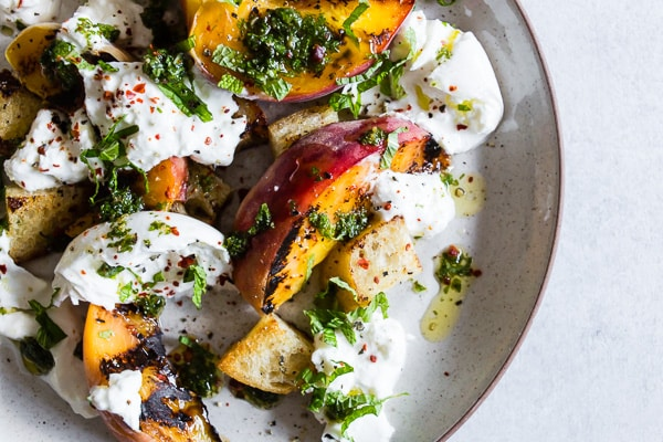 This grilled peach burrata salad is packed full of summer flavor and perfect as a side dish or light summer meal. Once you start grilling your peaches you'll never want to eat them plain again. Plus, they pair perfectly with creamy burrata cheese and fresh mint olive oil drizzle.